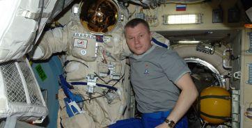 """Олег Новицкий и скафандр """"Орлан"""", в котором космонавты выходят с МКС в открытый космос"""
