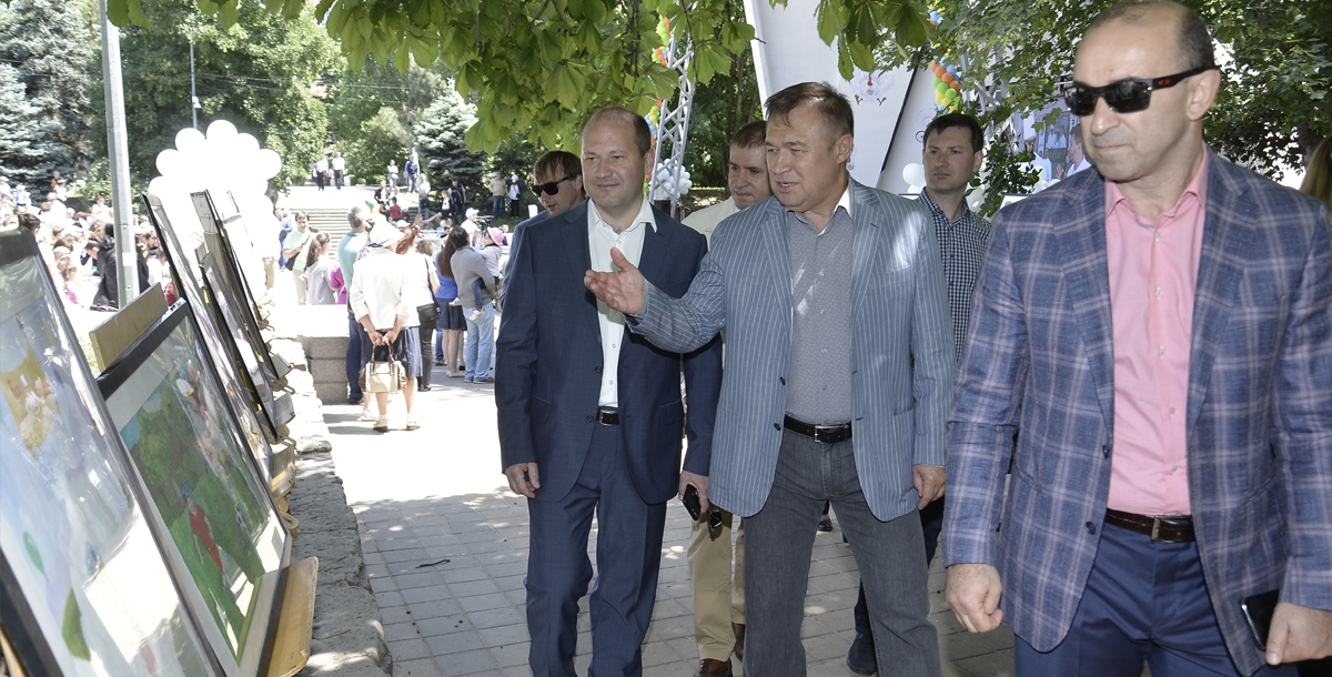 Вадим Ванеев, Виктор Гончаров, Александр Скрябин осматривают выставку рисунков.