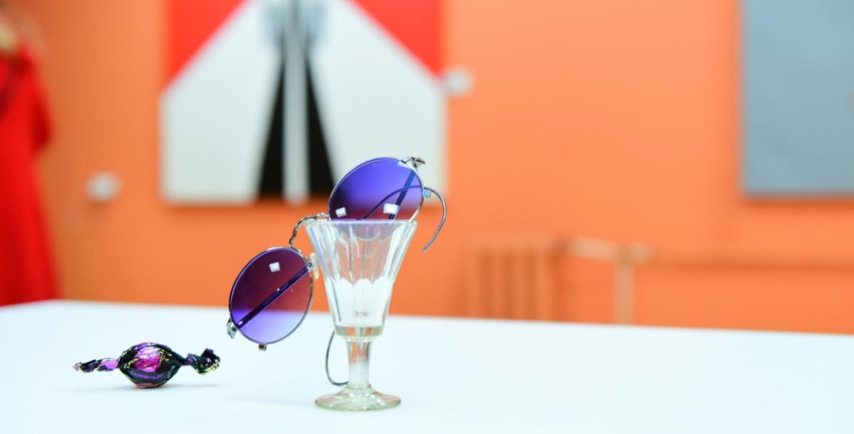 «Лепс спел» Пустая рюмка водки на столе и солнцезащитные очки с голубыми стеклами — «Лепс спел». Сотрудница музея рассказывает, что когда-то певец Григорий Лепс подарил Шнурову свои очки. И добавляет: «Но это не они». Я кладу возле рюмки конфету, и получается новая инсталляция «Лепс спел, не закусывая».